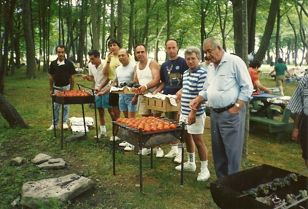 An old photo of a group of Armenian men grilled tomatoes at the park