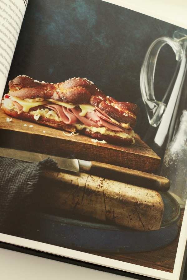 a sandwich made with pretzel bread, cold cuts, and mustard on a wooden board