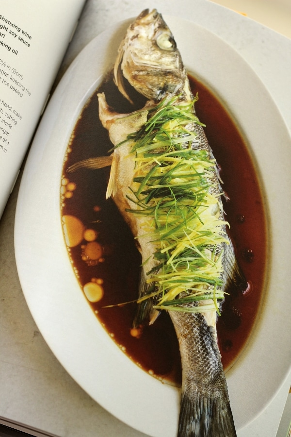overhead view of a whole fish topped with sliced greens surrounded with brown sauce