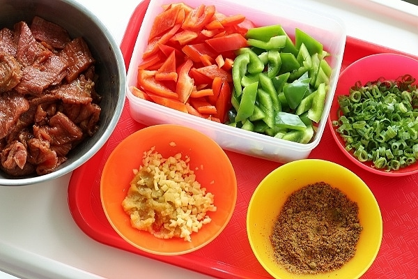 colorful containers filled with various ingredients like chopped peppers, spices, and beef