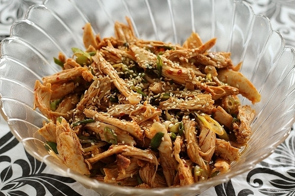 shredded chicken topped with sesame seeds in a large glass serving bowl