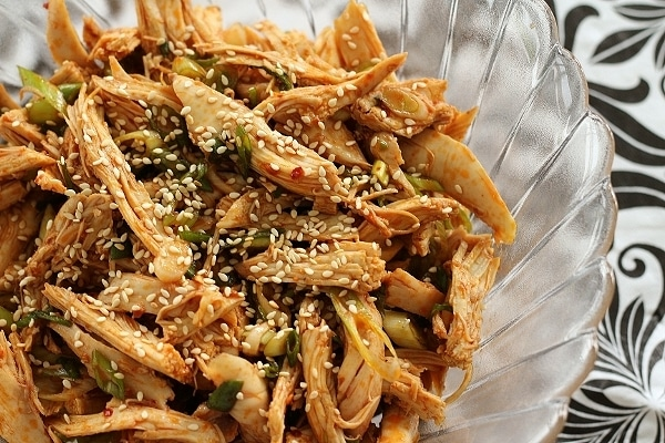 overhead closeup of shredded chicken with sesame seeds in a glass bowl