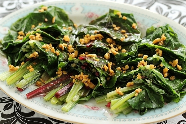 piles of cooked greens with chopped ginger on top served on an oval platter