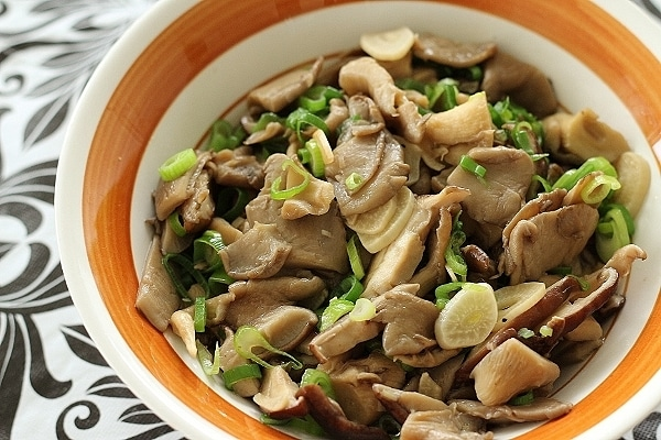stir-fried mushrooms with garlic and chicken in a brown and white bowl