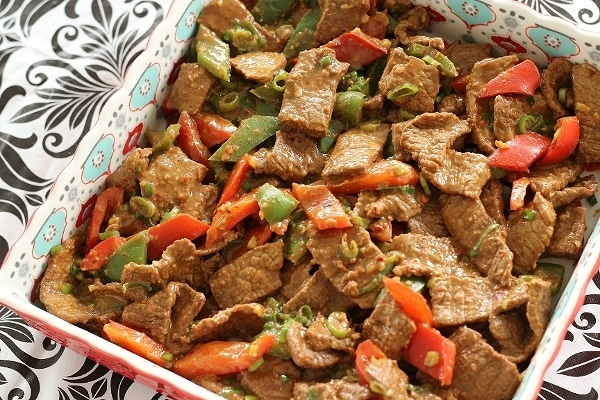 overhead view of cooked sliced beef with red and green peppers in a square serving dish