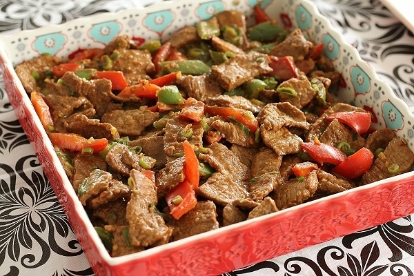 sliced beef with red and green peppers in a square serving dish with red edges