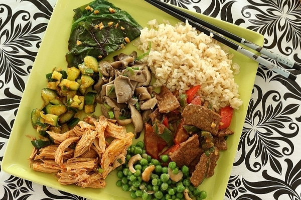 a square green plate topped with a variety of foods including rice, vegetables, chicken and beef