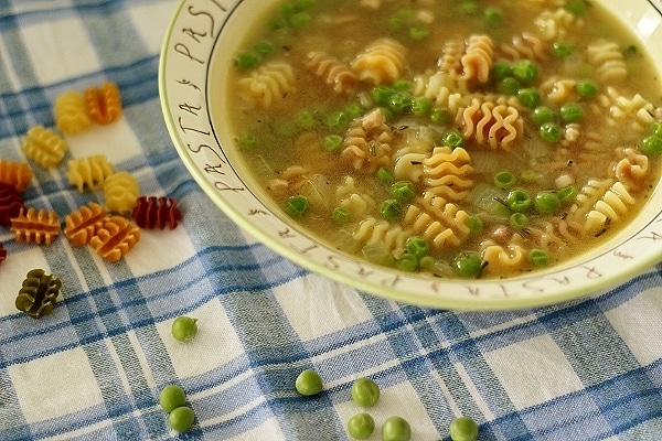closeup of a bowl of pea and pasta soup with peas and pasta spilled around it