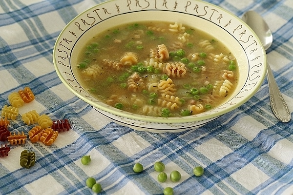 wide view of a bowl of pasta and pea soup on a blue and white surface