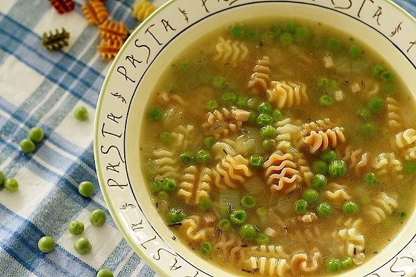 overhead view of a bowl of pasta and pea soup on a blue and white surface