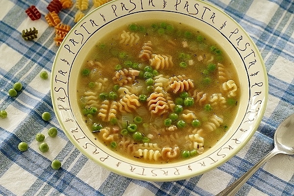 A bowl of soup with pasta and peas on a blue and white cloth