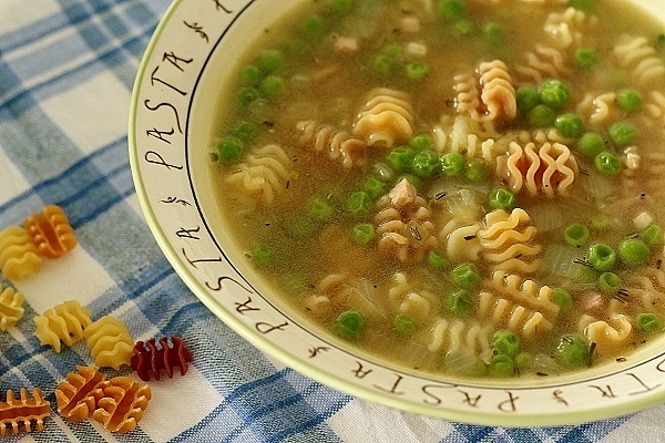 closeup of a bowl of pea and pasta soup with pasta spilled next to it