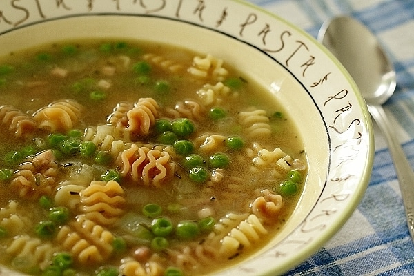 closeup of a bowl of soup with peas and pasta