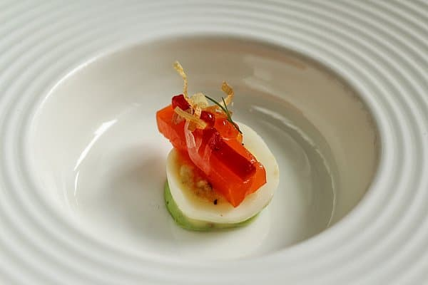 an artfully plated small bite of food on a white plate