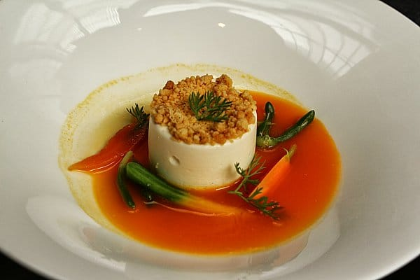 a cylindrical souffle topped with crumble and surrounded with carrot broth