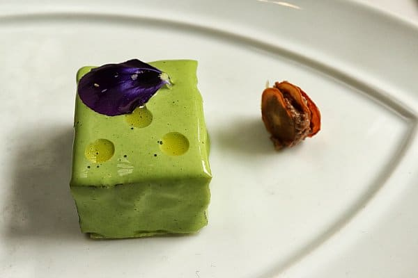 a small square bite of food on a plate with a purple flower petal on top