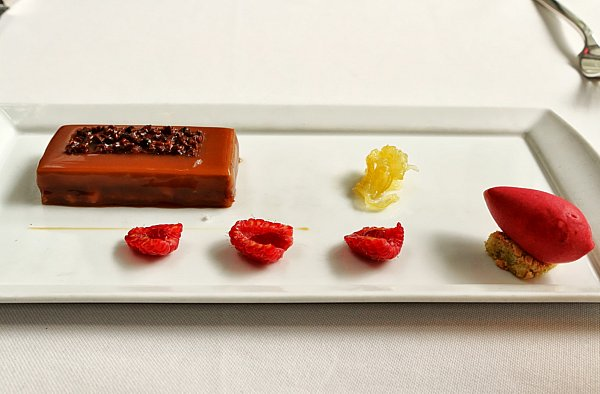 a long brown bar with raspberry halves on a white plate