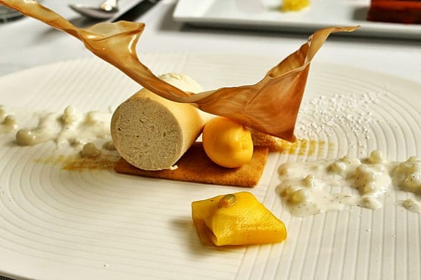 an artfully plated dessert with mango ice cream and a crispy sugar decoration