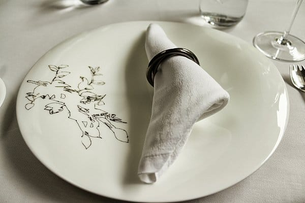a white plate topped with a white cloth napkin in a metal ring
