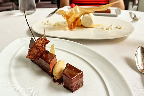 a chocolate dessert on a white plate with another dessert in the background