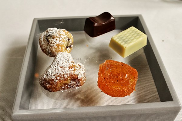 small bites of cookies and chocolates on a square glass plate