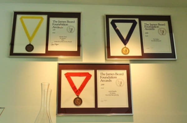 three awards and medals framed on a wall