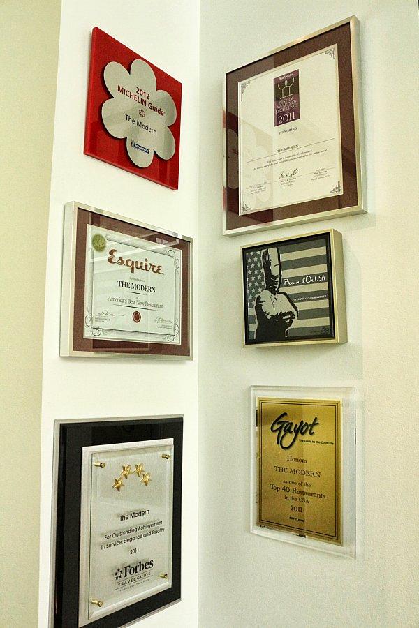 framed awards arranged on a wall