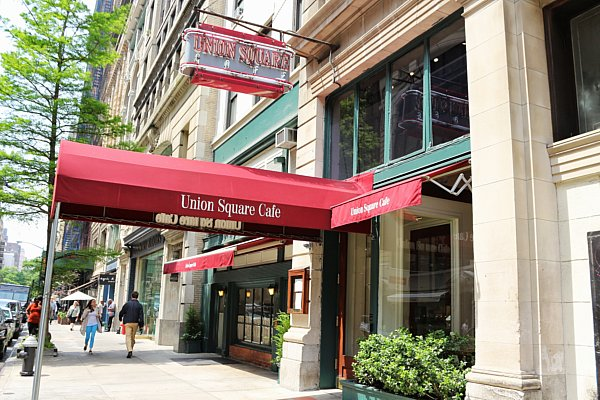 exterior of Union Square Cafe with red awning and white writing