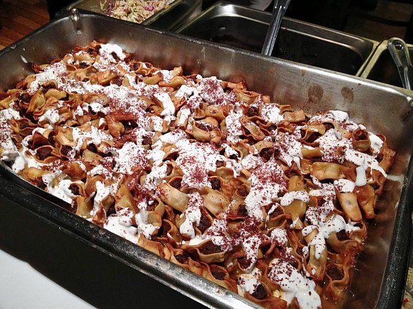 a large metal tray filled with food topped with yogurt sauce