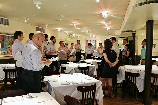 A group of people standing in a restaurant dining room
