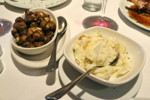 overhead view of bowls of sauteed mushrooms and mashed potatoes on a white surface