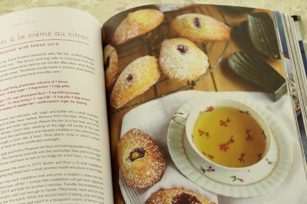 a cup of tea with small Madeleine cookies dusted with powdered sugar