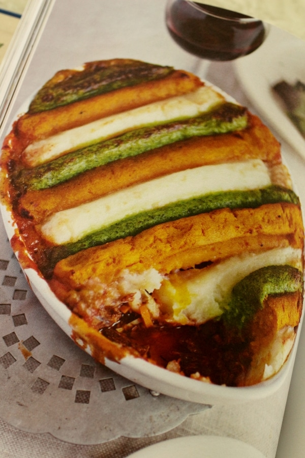 an oval casserole topped with green, orange, and white stripes of food piped onto it