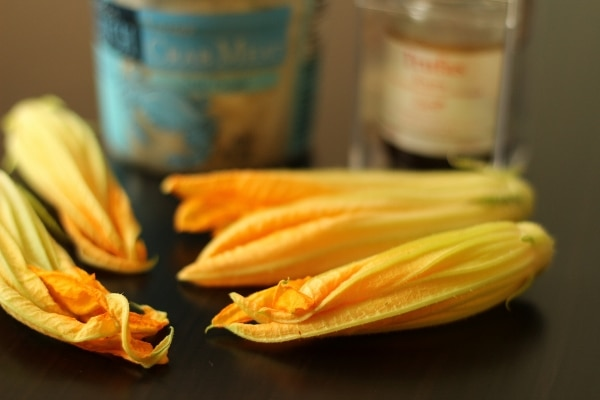 a closeup of raw zucchini blossoms on a black surface