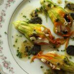 overhead closeup of stuffed zucchini flowers with black truffles on a china plate