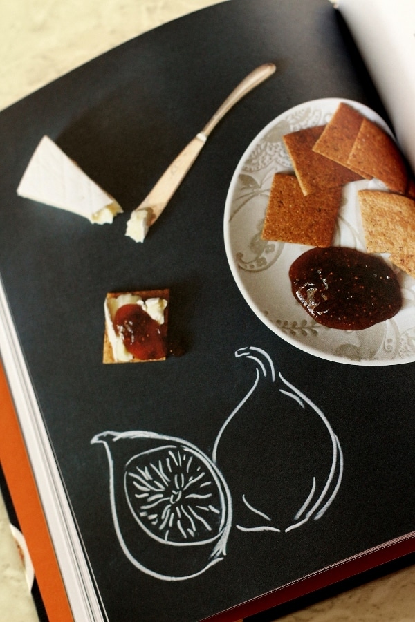 overhead view of square crackers with a scoop of jam on the side of the plate