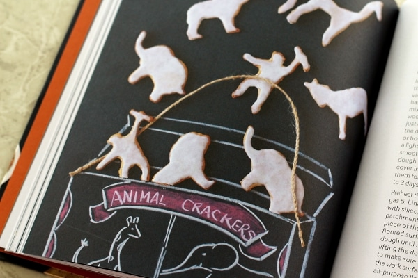 A closeup of animal crackers with white glaze on a black surface