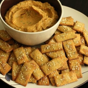 a bowl with a tan colored dip surrounded by rectangular crackers on a plate