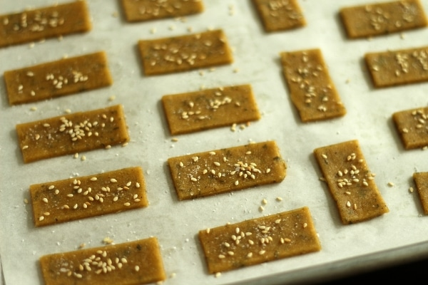 A closeup of unbaked rectangular crackers on a baking sheet