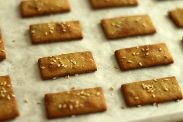 A closeup of baked rectangular crackers on a baking sheet