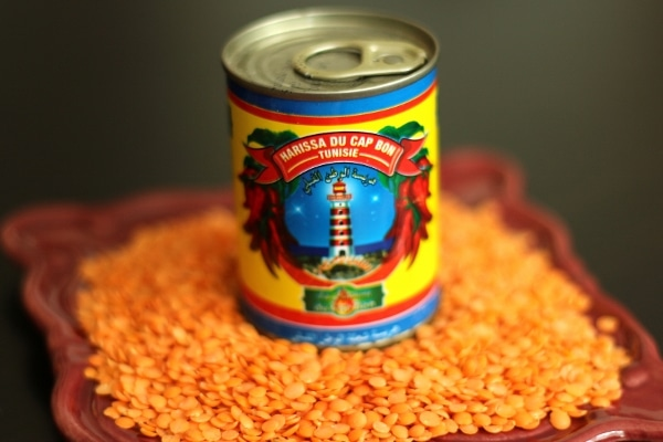 a can of harissa on a plate surrounded by uncooked red lentils