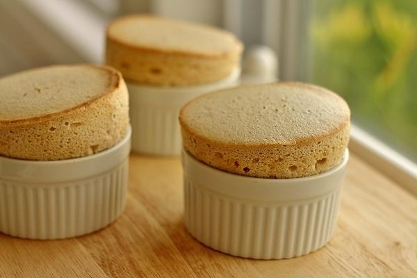 three souffles in white ramekins on a wooden board