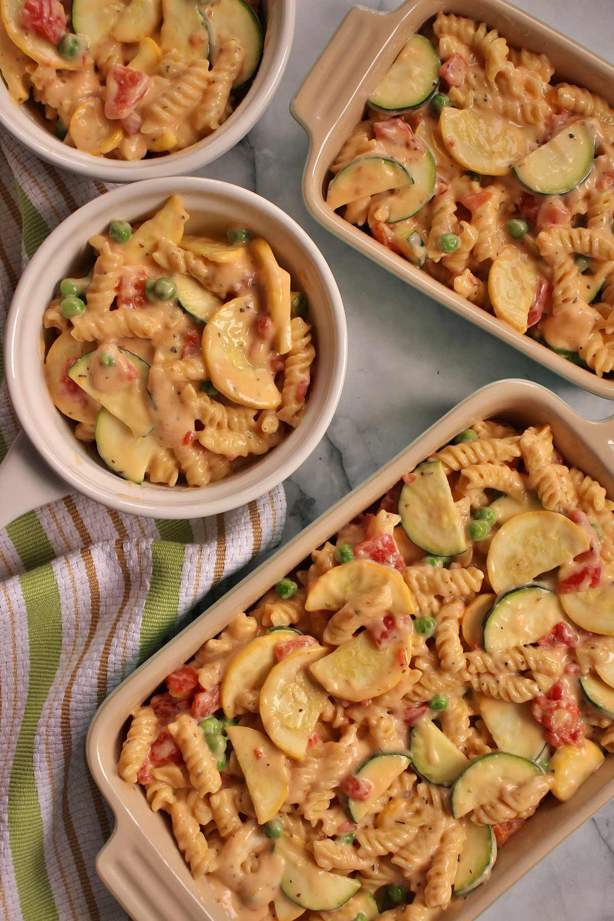 Veggie mac and cheese filled into 4 ceramic containers of various sizes and shapes.