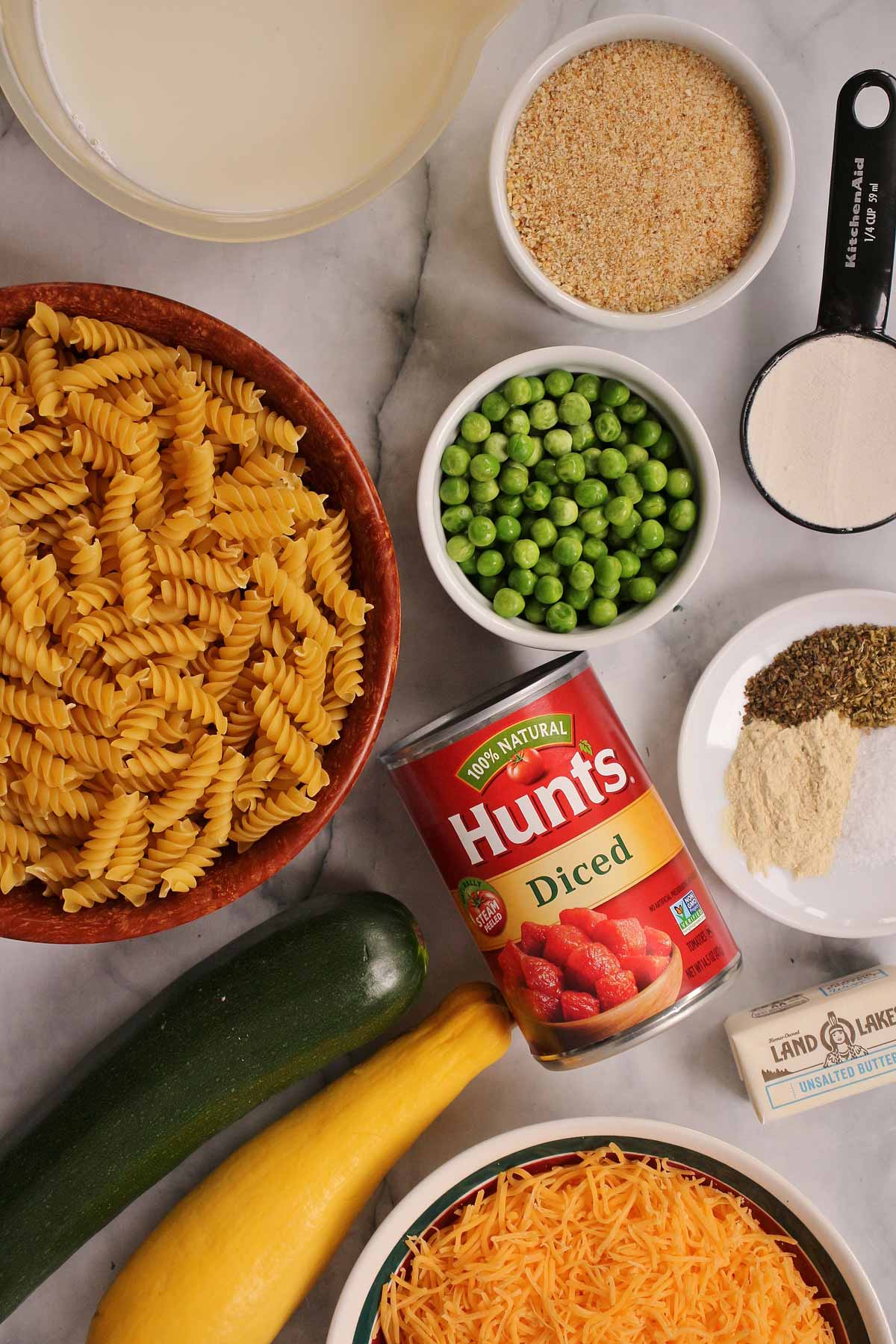 Rotini pasta, breadcrumbs, peas, zucchini, grated cheese, spices, butter, flour, and canned tomatoes.