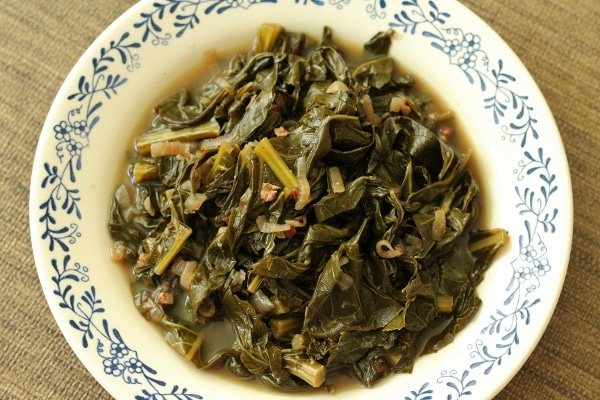 overhead view of braised collard greens in broth in a shallow white bowl