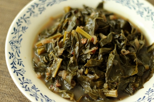 a shallow bowl piled high with braised collard greens in broth