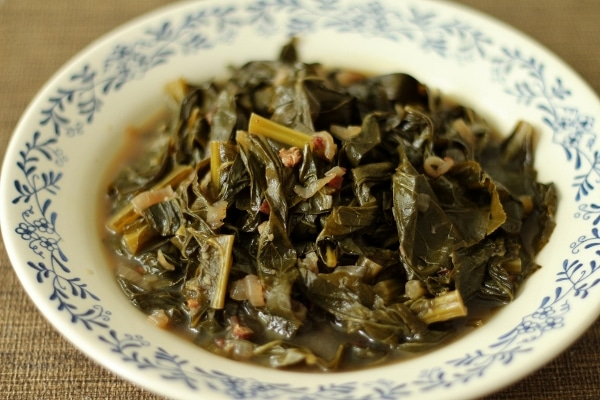 a white shallow bowl with blue trim filled with braised collard greens with broth