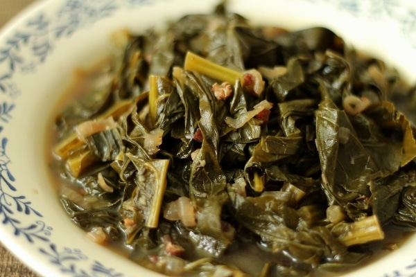 a closeup of braised collard greens in a murky broth in a shallow bowl