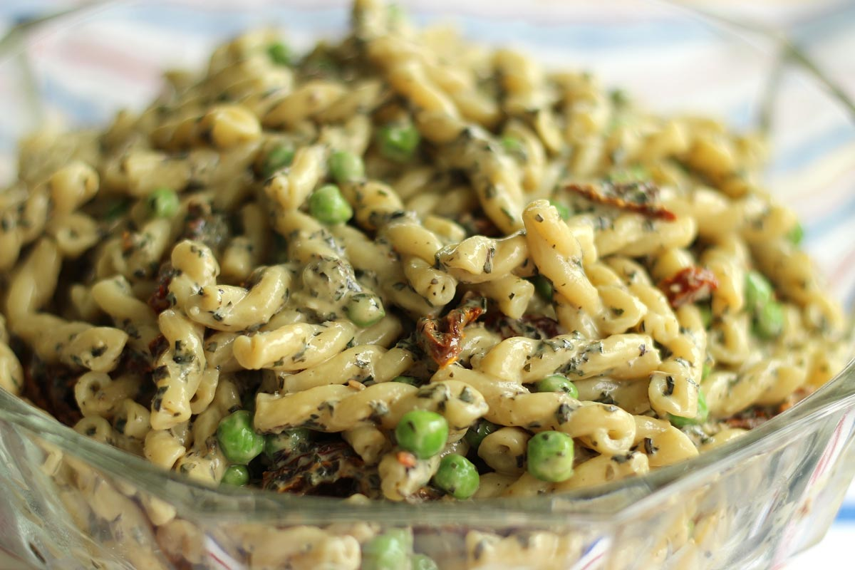 Closeup of pasta salad with pesto, peas, and sun-dried tomatoes in a glass bowl.