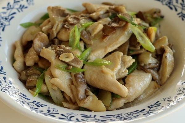 side view of stir-fried chicken with mushrooms and scallions in a shallow white dish